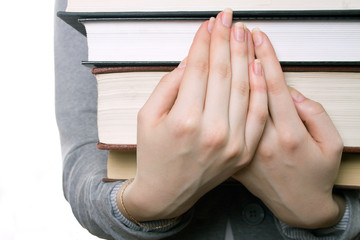 The girl holds a heavy pile of books on hands