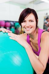 lächelnde frau mit gymnastikball im studio