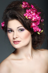 beautiful  brunette with pink orchids in hairs, cosmetics