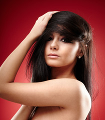 Sexy brunette with hands in her hair on red background