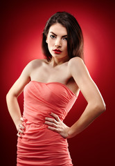 Beautiful brunette standing with hands on hips on red background