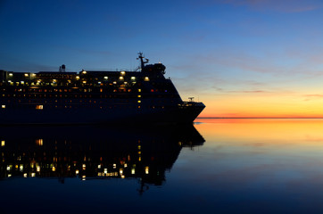 cruise ferry ship with it's reflection at the colorful sunset