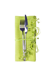 Knife and fork with green linen napkin isolated on white