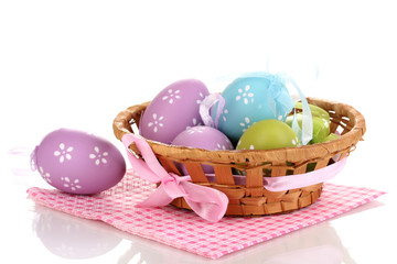 Colorful easter eggs in basket on napkin isolated on white