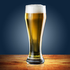 Glass of beer on blue background