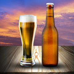 Glass and bottle of beer on wood table at sunset