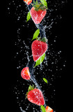 Strawberries in water splash, isolated on black background