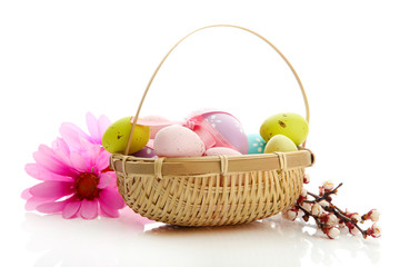 Beautiful easter eggs and apricot blossom in basket, isolated