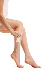 Beautiful woman legs with depilation cream, isolated on white