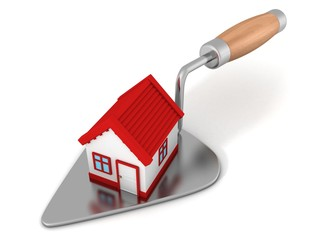 New house with red roof on construction trowel
