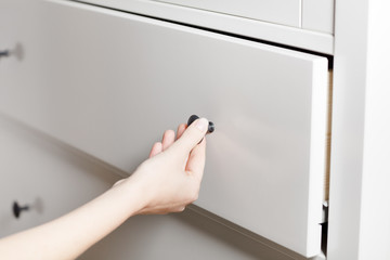 Close up of hand opening a white drawer