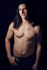 portrait of handsome man with long hair, torso naked on black ba