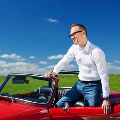 mann steigt in rotes cabrio