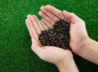 Heart shape made from coffee beans in hands on green background