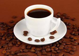 Cup of strong coffee on brown background