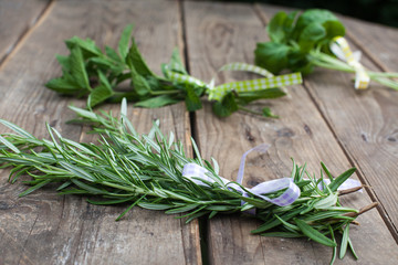 Rosemary, basil and pepermint plants on wooden table