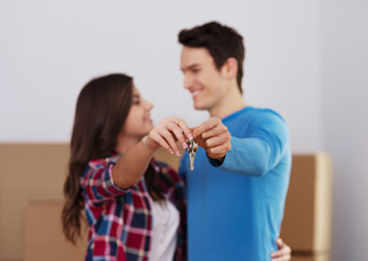 Young couple holding key to new home in hand