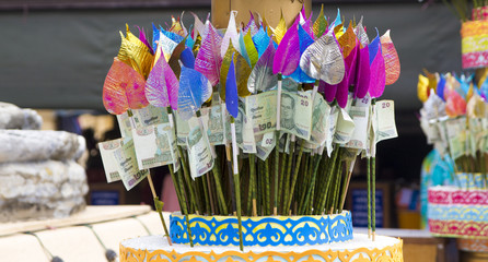 Money for making merit attached with colorful Bothi leaves
