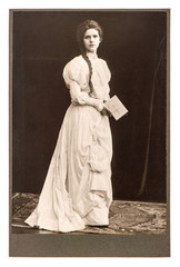 young woman in vintage dress posing with bible book