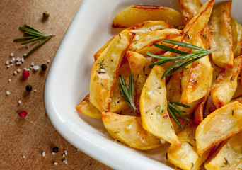 Roasted potatoes with rosemary in a white bowl