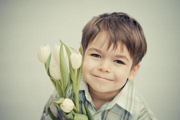 Obraz Uśmiechnięty chłopiec z tulipanami - fototapety do salonu