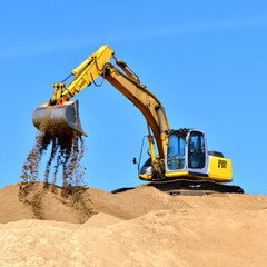 new yellow excavator working on sand dunes