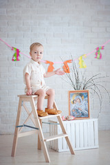 Little boy sitting on ladder on the background of Easter