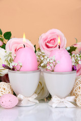 Easter candles with flowers on beige background