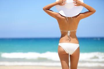 Beach vacation - hot woman in sunhat and bikini