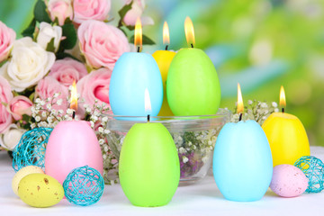 Easter candles with flowers on bright background