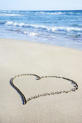 heart outline on sand against wave