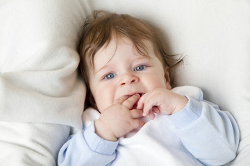 Little Baby is looking to camera. He is lying on a white pillow. Studiolight