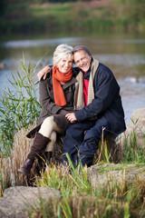 glückliches paar sitzt am see