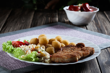 Breaded chop, prepared potatoes and salad. Mysterious light