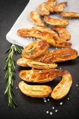 Fried potatoes with herbs and salt on a board slate