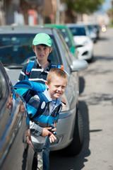 schulkinder zwischen parkenden autos