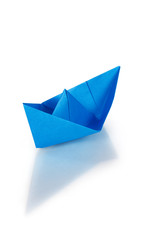 Blue paper ship on a glass with reflection