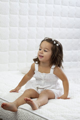 smiling little girl sitting on bed