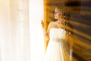 sunlight beautiful young bride is at a wedding in the room by wi
