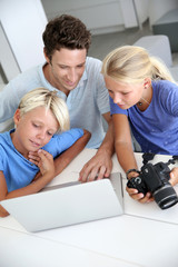 Man with teenagers looking at pictures on computer