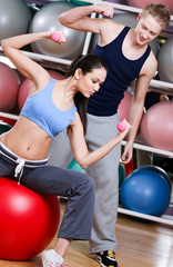 Woman exercises sitting on the gym ball in fitness gym