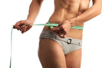 Cropped view of young fitness woman with measuring tape