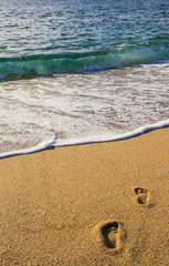 Pieds nus dans le sable, rouleaux et écume