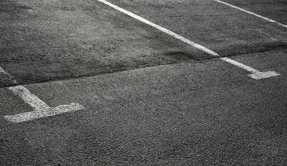Empty parking places on dark asphalt