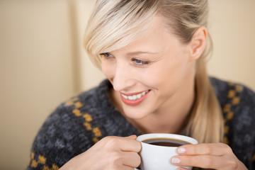 lächelnde frau genießt ihren kaffee