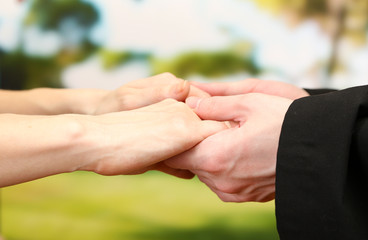 Priest holding woman hands, on green background