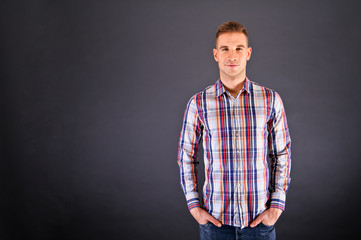 Man overdark background in squared shirt