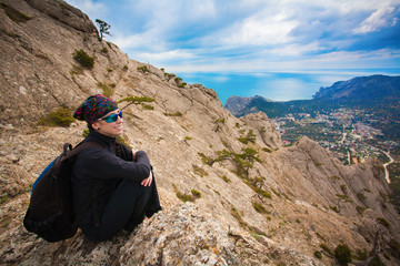 Girl tourist enjoys the view from the mountain top