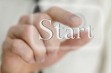 Businessman hand pressing Start icon