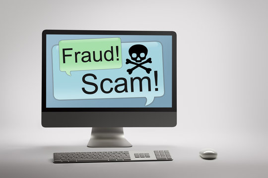Computer displaying internet fraud and scam warning on screen